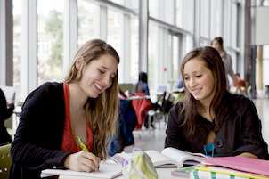 Two students in a library studying in Quebec, Canada with their CAQ and study permit